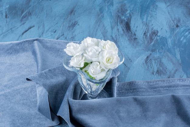 Een glazen vaas met kunstbloemen op tafelkleed.