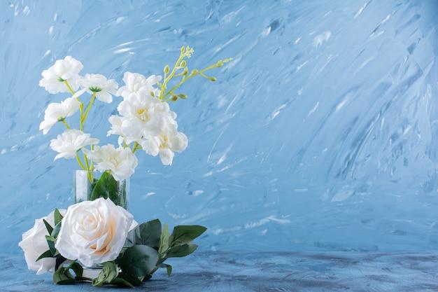 Een glazen vaas met mooie frisse witte roze bloemen op blauw.