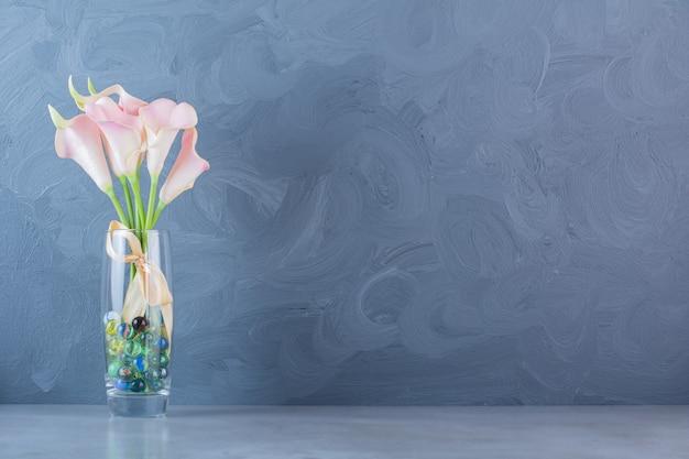 Een glazen vaas van roze mooie bloemen met strik en kleurrijke bolletjes.