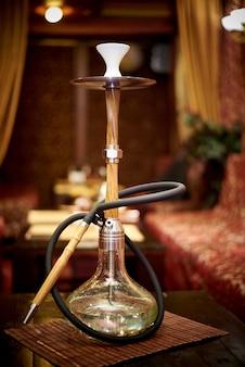 Een glazen waterpijp staat op de tafel in de loungebar