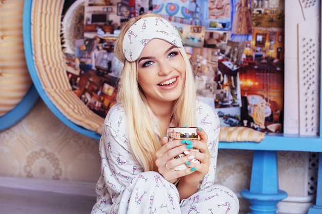 Een glimlachend blondemeisje zit op de vloer in een pyjama en drinkt koffie. slaapmasker. concept levensstijl, rust, ontbijt, slaap.