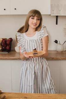 Een glimlachend huisvrouwenmeisje in een grijs schort staat in de keuken en houdt een bord met dessert vast