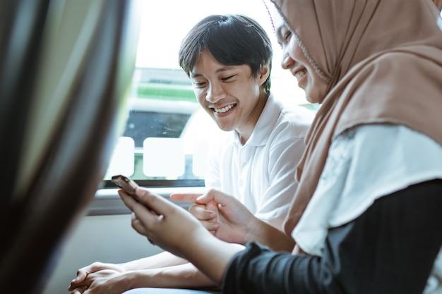Een glimlachend jong moslimpaar dat samen naar het scherm van de mobiele telefoon kijkt terwijl ze in de bus zitten
