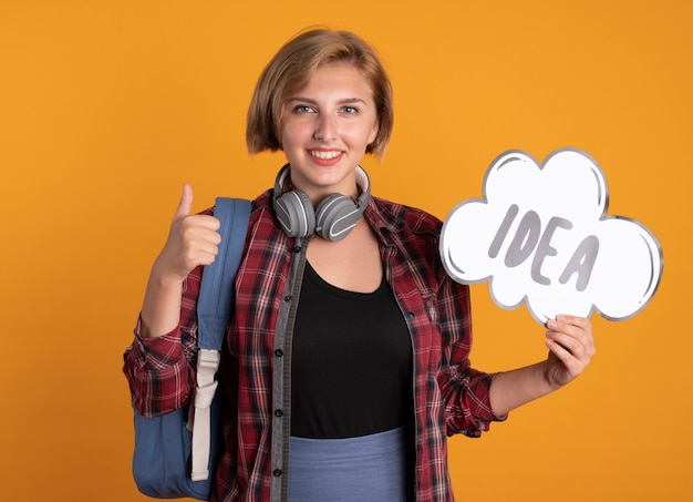 Een glimlachend jong slavisch studentenmeisje met een koptelefoon die een rugzak draagt, houdt een ideebel omhoog