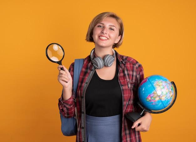 Een glimlachend jong slavisch studentenmeisje met een koptelefoon die een rugzak draagt, houdt een vergrootglas en een wereldbol vast
