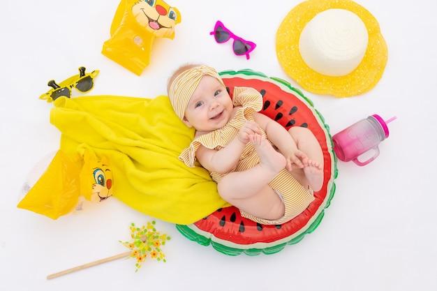 Een glimlachend kind met een zwemmende ring in een zwembroek, handdoek en zonnebril ligt op een witte geïsoleerde achtergrond
