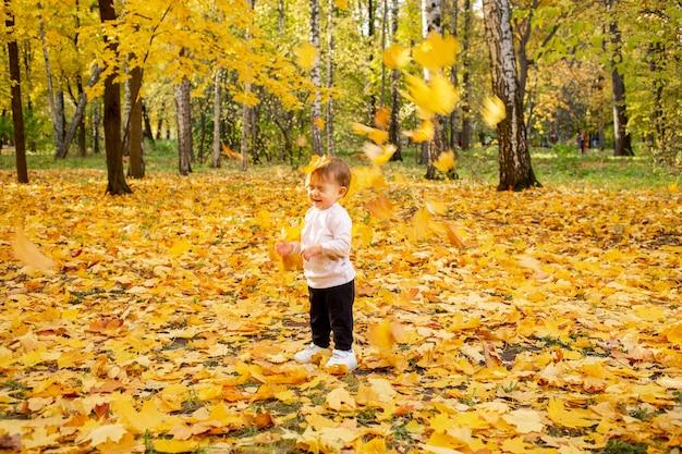 Een glimlachend klein meisje met gesloten ogen staat in het herfstpark. gele esdoornbladeren vallen op haar neer