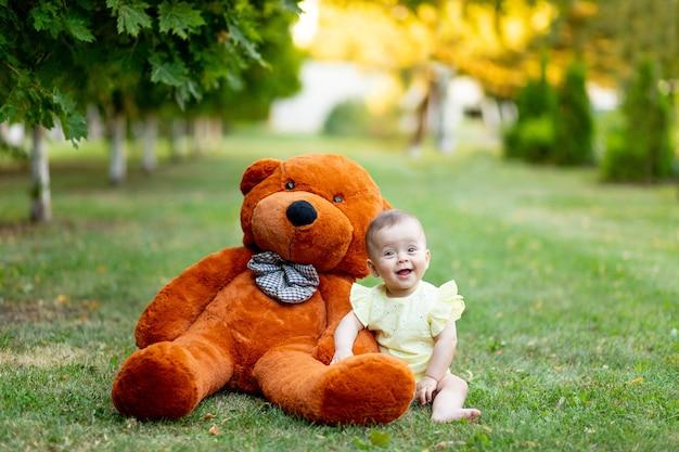 Een glimlachend klein meisje zit in de zomer op het groene gras met een grote teddybeer in een gele zomerjurk.