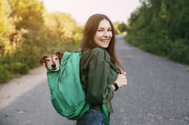 Een glimlachend meisje houdt een groene rugzak op haar schouder, van waaruit een schattige hond uitkijkt