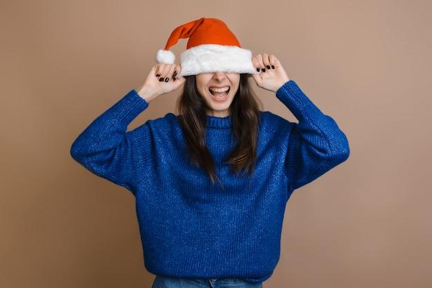 Een glimlachend meisje trok de hoed van de kerstman aan haar ogen. op een bruine achtergrond.