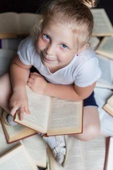 Een glimlachend meisje zit op de vloer met boeken. onderwijs en training.