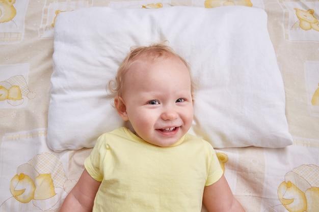 Een glimlachende baby ligt op een wit kussen.