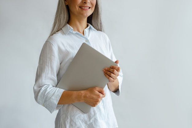 Een glimlachende dame van middelbare leeftijd die een elegante blouse draagt, houdt een moderne laptop vast op een lichtgrijze achtergrond in de studioclose-up, ruimte voor tekst