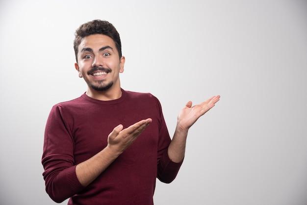 Een glimlachende donkerbruine mens die zijn hand op grijs toont.