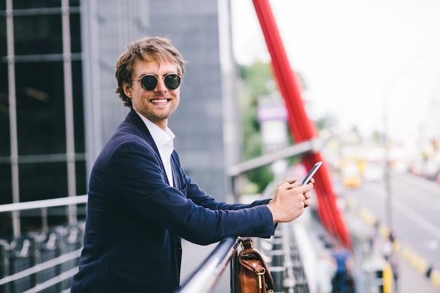 Een glimlachende en gelukkige manager staat op straat met een koffer