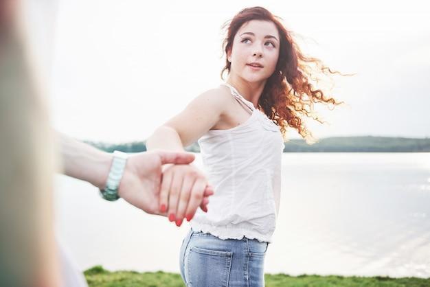 Een glimlachende gelukkige vrouw met een speelse uitdrukking en een hand met haar man.