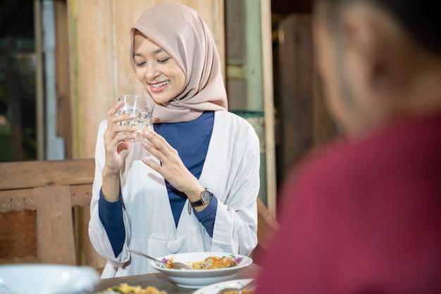 Een glimlachende gesluierde vrouw die een glas vasthoudt terwijl ze drinkt voor iftar