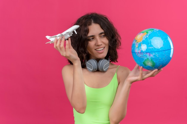 Een glimlachende jonge aantrekkelijke vrouw met kort haar in groene crop top in koptelefoon speelgoed vliegtuig te houden en globe te kijken