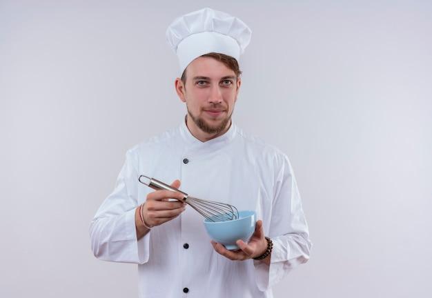 Een glimlachende jonge, bebaarde chef-kokmens die wit fornuisuniform draagt en de mixerlepel van de hoedholding op een blauwe kom terwijl het kijken op een witte muur