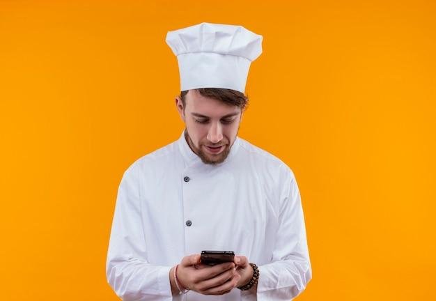 Een glimlachende jonge, bebaarde chef-kokmens in wit uniform kijkt naar zijn mobiele telefoon terwijl hij op een oranje muur staat