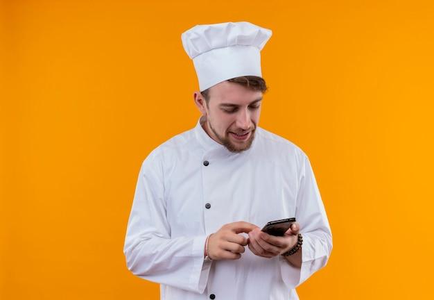 Een glimlachende jonge, bebaarde chef-kokmens in wit uniform wat betreft zijn mobiele telefoon op een oranje muur
