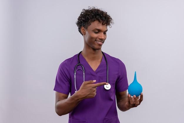Een glimlachende jonge knappe dokter met een donkere huid en krullend haar in violet uniform met een stethoscoop die duimen naar beneden toont terwijl hij met wijsvinger naar een klysma wijst