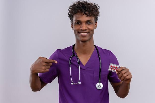 Een glimlachende jonge knappe donkere arts met krullend haar die violet uniform draagt met een stethoscoop die op pillen met wijsvinger richt
