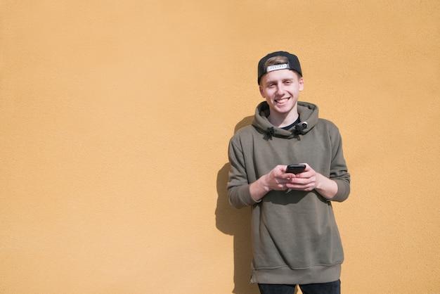 Een glimlachende jonge man staat op een oranje muur met een telefoon in zijn handen en glimlacht.