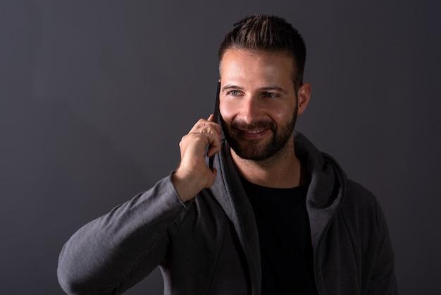 Een glimlachende jonge mens die op zijn telefoon spreekt
