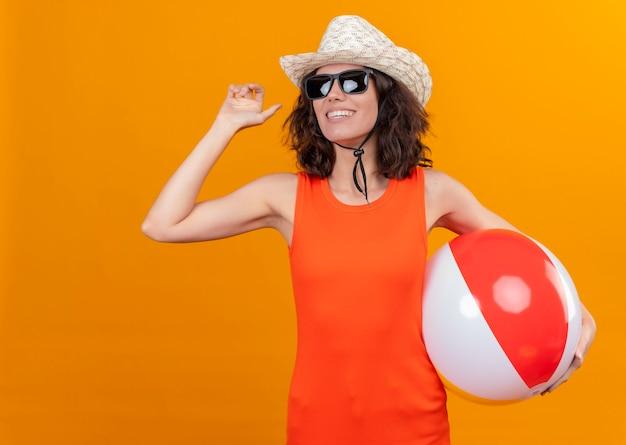 Een glimlachende jonge vrouw met kort haar in een oranje overhemd dat zonnehoed en zonnebril draagt die opblaasbare bal houdt die met hand vaarwel toont