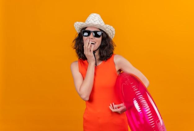 Een glimlachende jonge vrouw met kort haar in een oranje overhemd dat zonnehoed en zonnebril draagt die opblaasbare ring houdt die hand op gezicht houdt