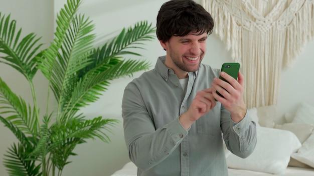Een glimlachende jongeman met een smartphone zit op het bed en viert succes thuis of ontvangt goed nieuws