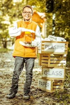 Een glimlachende jongen die een kruik met gebruikte batterijen houdt om op een gelukkige dag te recyclen