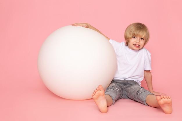 Een glimlachende jongen van het vooraanzichtblonde in het witte t-shirt spelen met ronde witte bal op het roze bureau