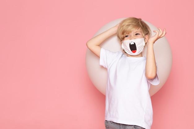 Een glimlachende jongen van het vooraanzichtblonde in witte t-shirt en grappig masker op de roze ruimte
