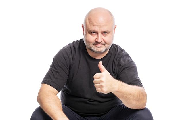 Een glimlachende kale man van middelbare leeftijd in een zwart t-shirt zit met zijn duim omhoog. over wit wordt geïsoleerd.