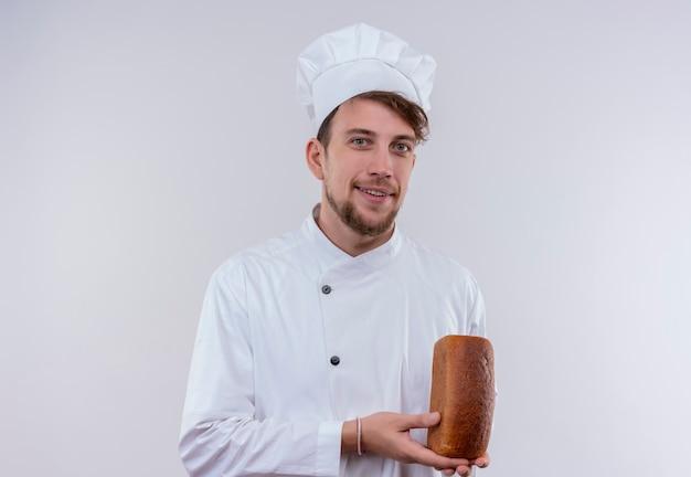 Een glimlachende knappe jonge, bebaarde chef-kokmens in wit fornuisuniform en hoed die een brood vasthoudt terwijl hij op een witte muur kijkt
