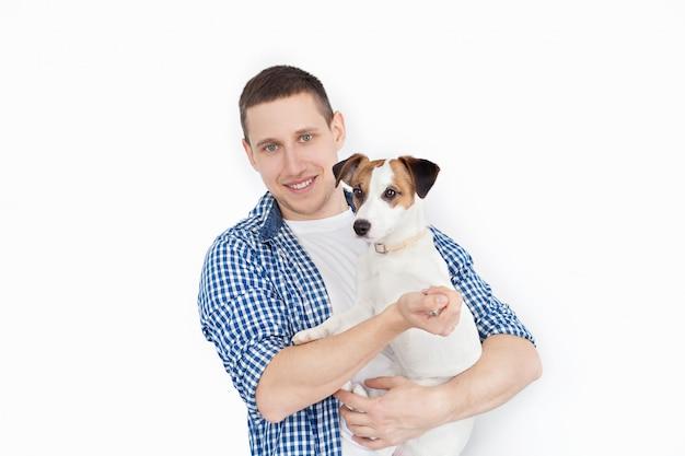 Een glimlachende knappe mens die een rashond op een wit houdt. het concept van mensen en dieren. jonge man met zijn hond in zijn armen met liefde en spelen met hem, tegen een wit