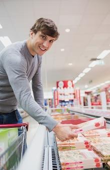 Een glimlachende man die een product kiest
