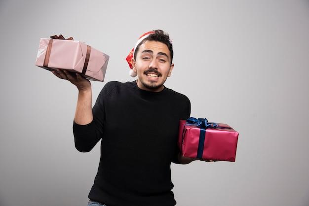 Een glimlachende man met een kerstmuts met een nieuwjaarsgeschenken.