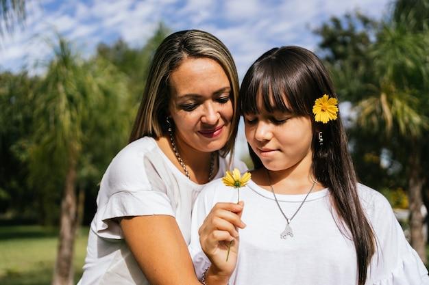 Een glimlachende moeder en dochter met een bloem, buitenshuis.