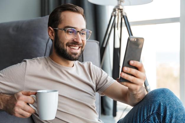 Een glimlachende optimistische jongeman die binnenshuis koffie drinkt met behulp van mobiele telefoon.