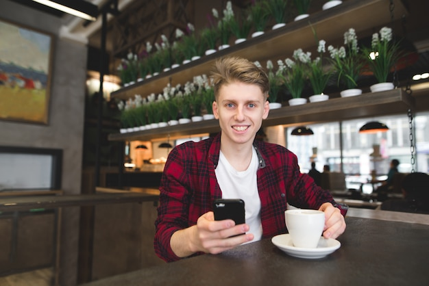 Een glimlachende studentenzitting in een koffie met een kop van koffie en een smartphone in zijn handen