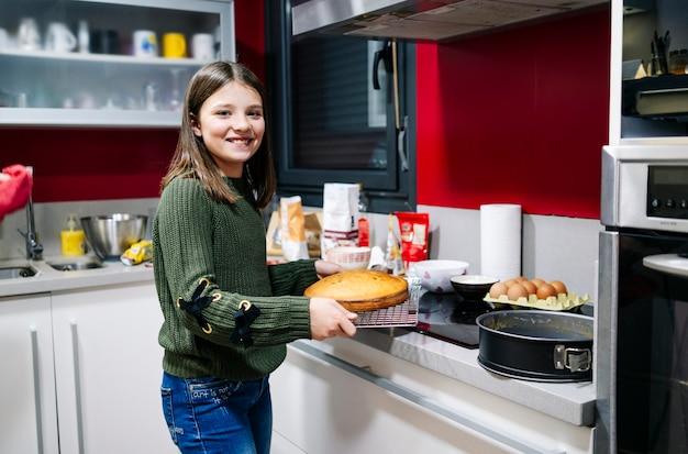 Een glimlachende tiener die een biscuitgebak in de keuken kookt