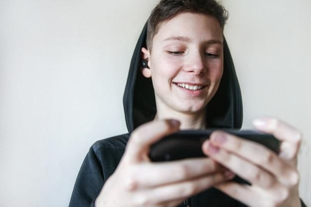 Een glimlachende tiener in een zwarte kap en koptelefoon praat aan de telefoon