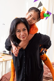 Een glimlachende vrouw die een meisje draagt dat naar de camera kijkt in vermomming van halloween