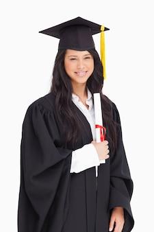 Een glimlachende vrouw die haar graad houdt aangezien zij van universiteit heeft een diploma behaald