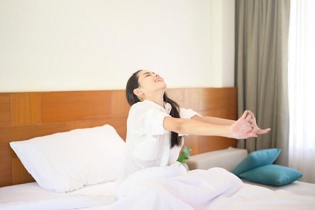 Een glimlachende vrouw die haar handen uitrekt nadat ze 's ochtends thuis wakker werd.