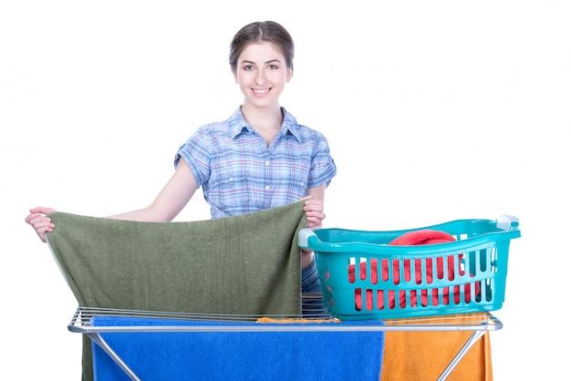 Een glimlachende vrouw die handdoeken te drogen zet.