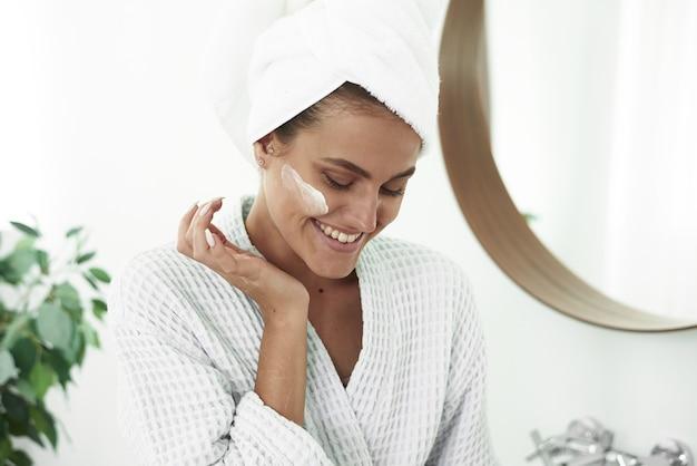 Een glimlachende vrouw in een badjas en een handdoek op haar hoofd brengt in de badkamer vochtinbrengende crème uit een potje op haar gezicht aan.